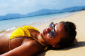Young woman sun bathing on a sandy beach of thailand in yellow swimsuit and sunglasses laying down sunny summer day Stock Photography
