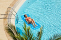 Young woman sunbathes lying on inflatable mattress in red swimsuit water near to edge of pool Royalty Free Stock Photo