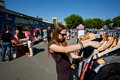 Young woman in sunglasses chooses second hand dress during the city flea market Stock Images