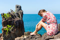 Young  woman with sunglasses sitting on rocks near the sea. Royalty Free Stock Photo