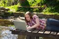 Young woman surfs in the garden lying on pond and with her laptop Stock Photos