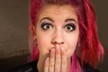 Young woman in suspense punk rocker pink hair with hand on mouth Royalty Free Stock Photography