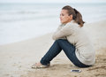 Young woman in sweater with cell phone sitting on lonely beach and looking into distance Royalty Free Stock Images