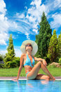 Young woman by the swimming pool relaxing Royalty Free Stock Images