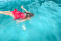 A young woman swimming under water in red dress in the pool Stock Photos