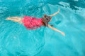 A young woman swimming under water in red dress in the pool Royalty Free Stock Photo