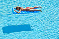 Young woman in swimsuit bakes lying on inflatable mattress red pool Royalty Free Stock Image
