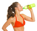 Young woman in swimsuit drinking bottle of water isolated on white Royalty Free Stock Photo
