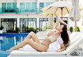 Young woman in swimsuit laying on chaise longue Royalty Free Stock Image