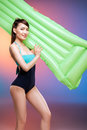 Young woman in swimsuit posing with swimming mattress and smiling at camera Royalty Free Stock Photo