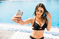 Young woman in swimsuit relaxing with cocktail near pool and take selfie on phone. Summer time Royalty Free Stock Photo