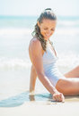 Young woman in swimsuit sitting on sea shore and drawing on sand pretty white Stock Photography