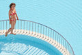 Young woman in swimsuit walks on ledge separating pools red two Stock Photography