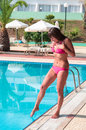Young woman in swimwear shudders at the feet touch of cold water pool Royalty Free Stock Photos