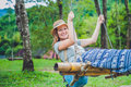 Young woman is swinging on a swing in summer pine forest. Image toned Royalty Free Stock Photo