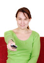 Young woman switches with remote control on red sofa Stock Photos