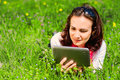 Young woman with tablet relaxing in nature and using a digital Royalty Free Stock Images