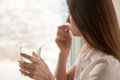 Young woman takes pill with glass of water in hand Royalty Free Stock Photo
