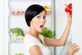 Young woman takes red pepper from opened fridge Stockbilder