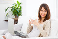 Young woman taking a cofee in the sofa with a laptop businesswoman working at home Royalty Free Stock Photo