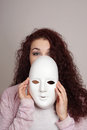 Young woman taking off mask shy plain white Stock Images