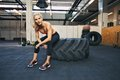 Young woman taking rest after crossfit workout fit lady sitting on a big tire her exercise at gym Royalty Free Stock Photos