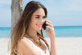 Young woman talking on cellphone happy at beach Stock Photography