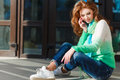 Young woman talking on mobile phone beautiful with red curly long hair and green eyes light makeup and pink nail polish dressed in Royalty Free Stock Images