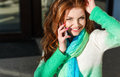 Young woman talking on mobile phone beautiful with red curly long hair and green eyes light makeup and pink nail polish dressed in Stock Photography