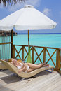 Young woman tans on villa on ocean Maldives Royalty Free Stock Photography