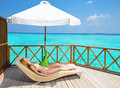 Young woman tans on villa on ocean Maldives Royalty Free Stock Photo