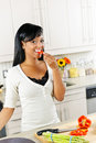 Young woman tasting vegetables in kitchen Stock Photos