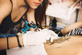 Young Woman Tattooer Showing P...