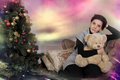 Young woman with teddybear sitting on a couch at the christmas tree Stock Images