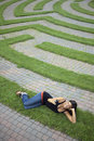 Young Woman Text Messaging in a Grass Maze Royalty Free Stock Photo