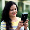 Young woman texting with her cellphone at outdoo Royalty Free Stock Photo