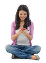 Young woman texting on smart phone smiling and her mobile sitting isolated over white background Stock Images
