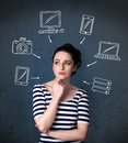 Young woman thinking with drawn gadgets around her head thoughtful multimedia icons Stock Photography