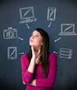 Young woman thinking with drawn gadgets around her head thoughtful multimedia icons Stock Images