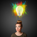 Young woman thinking with lightbulb above her head pretty gesturing and paint splashes Royalty Free Stock Images