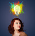 Young woman thinking with lightbulb above her head pretty gesturing and paint splashes Stock Image