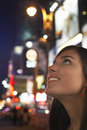 Young woman in times square new york at night closeup of a smiling looking up Stock Photos