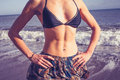 Young woman with toned abs standing on the beach in bikini is Stock Photo