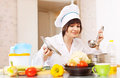 Young woman in toque cooks from vegetables with ladle kitchen Stock Photo