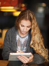 Young woman with touch screen tablet computer in cafe Royalty Free Stock Images
