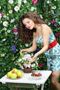 Young woman touches bunch of flowers on table next to green hedge Royalty Free Stock Photography