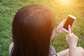 Young woman touching smartphone on green grass Royalty Free Stock Photo
