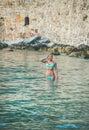 Young woman tourist enjoying sea at beach near fortress wall