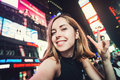 Young woman tourist laughing and taking selfie photo in New York City, Manhattan, Times Square