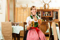 Young woman in traditional bavarian tracht in restaurant or pub with beer and steins and pretzel Stock Images